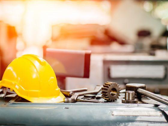 黄色安全帽,带工具在桌上的一家机械工厂在后台